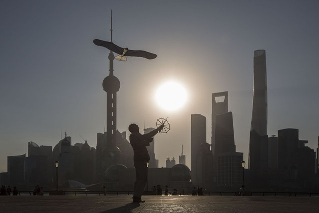 A man flies a kite on the Bund while buildings of Pudong's Lujiazui financial district stand across the Huangpu River as the sun rises in Shanghai, China, on Friday, October 2, 2015. (Photo by Qilai Shen/Bloomberg)