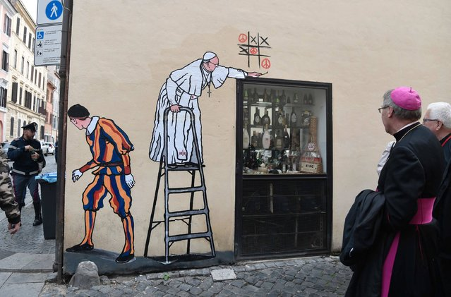 A bishop walks past a new street-art collage by Italian artist Maupal showing Pope Francis playing tic-tac-toe and drawing peace signs as a Swiss guard keep watches the street near the Vatican on October 19, 2016 in Rome. (Photo by Tiziana Fabi/AFP Photo)