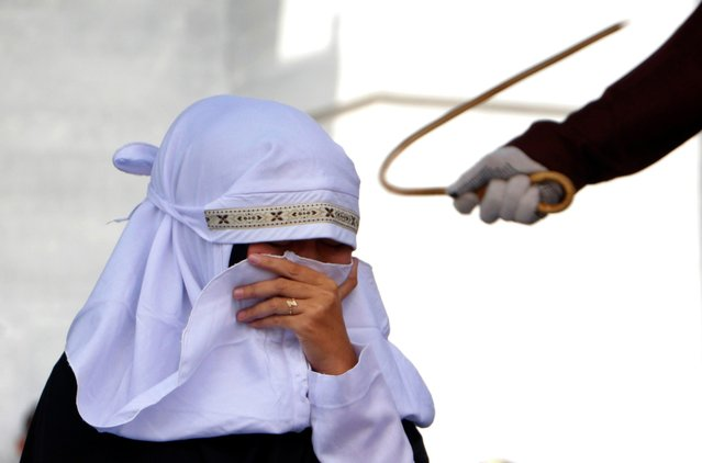 "An Acehnese woman covers her face as she is caned in public for violating sharia law in Banda Aceh, Indonesia, 20 April 2018. In Aceh - a deeply conservative province in Muslim-majority Indonesia - two women accused of prostitution were caned 11 times each. Three unmarried couples accused of ""flirtatious behaviour"" also received between 11 and 22 strokes. Shariah police wanted to convict the couples of ""zina"" – unlawful sexual intercourse that includes s*x outside marriage and adultery – which would have resulted in a greater number of lashes, but they lacked enough witnesses. One of the two women convicted of prostitution held up her hands after the fifth lash to signal that the pain was too intense. After a quick break she was given a drink and painfully lashed another six times. Members of the crowd, which included tourists from Malaysia, cheered enthusiastically at each blow and recorded the punishment with their smartphones. Aceh is the only part of Indonesia to enforce Sharia law. The province's actions were condemned by many and the governor of Aceh announced earlier this month that punishments would be moved indoors. After this display last week, canings will likely only happen in prisons where the public can't see them. Many residents are opposed to hiding them, believing it will reduce the deterrent and cause more people to violate Shariah law. (Photo by Raihal Fajri/EPA/EFE)"