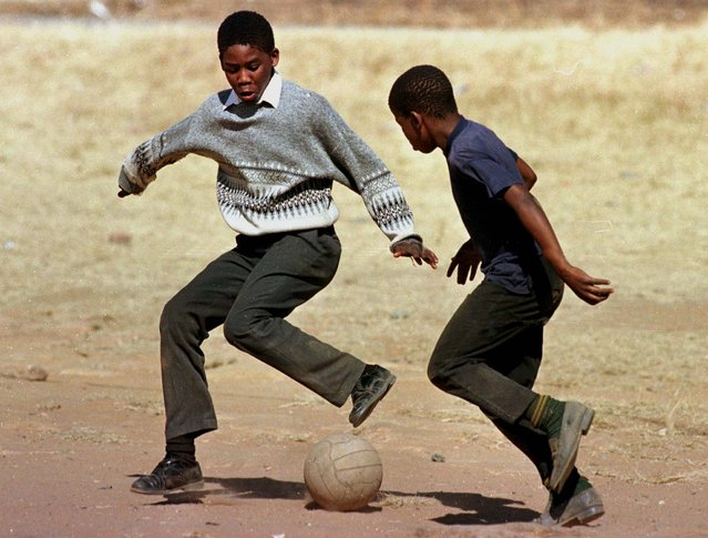 Two school children dreaming of stardom play soccer with an old weathered ball in the yard of a Soweto school June 12, as South Africans await their team's first-ever match in the World Cup finals. (Photo by Juda Ngwenya/Reuters)