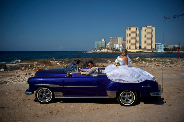 In this April 12, 2018 photo, newly-weds Dariel Verdecia, a 24-year-old computer engineer, and Roxana Cruz, a 26-year-old chemical engineer, pose for their wedding portraits in a vintage American car on the coast of Havana, Cuba. The couple said President Raul Castro's stepping down will be another step forward in Cuba's history, giving an entrance to new generations, and have hope the economy will continue growing. (Photo by Ramon Espinosa/AP Photo)