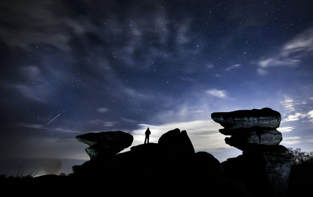 A man watches a meteor during the Geminid meteor shower over Brimham Rocks, a collection of balancing rock formations in the Nidderdale Area of Outstanding Natural Beauty in North Yorkshire on December 15, 2020. The Geminid meteor shower is active between 4th and 17th of December and is regarded as one of the most reliable of the year with as many as 70 meteors an hour. Brimham Rocks rocks began forming roughly 320 million years ago, when water, grit, and sand washed down from Scotland and Norway. However, standing nearly 30 feet tall the bizarre formations that can be seen today were created as the millstone grit was eroded during the last glacial period. (Photo by Danny Lawson/PA Images via Getty Images)