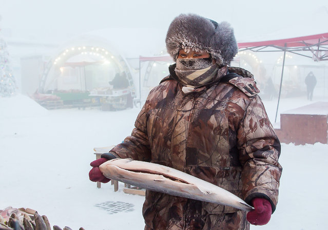 A vendor sells fish at Central Market in freezing conditions of minus 43 degrees Celsius in the city of Yakutsk, Sakha (Yakutia), Russia on December 13, 2020. The winters in Yakutsk are extremely cold and long and the summers short and warm, with temperatures sometimes rising above 30C. (Photo by Yevgeny Sofroneyev/TASS)