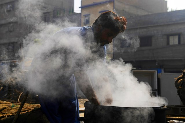 A vendor boils water chestnuts in a drum to sell at a workplace in Karachi on December 8, 2020. (Photo by Asif Hassan/AFP Photo)
