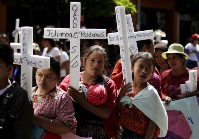 Women hold makeshift crosses during a march to commemorate International Day for the Elimination of Violence Against Women, in Guatemala City, November 25, 2015. (Photo by Josue Decavele/Reuters)