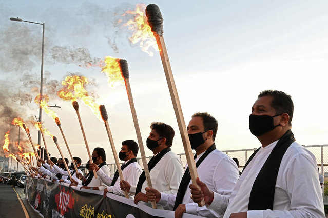 Sri Lanka's main opposition legislators wearing black masks and black scarfs hold torches during protest outside President Gotabaya Rajapaksas office in Colombo December 7, 2020. The opposition accused the government of the suppression of dissident using the pandemic as an excuse to curtail individual freedoms and free speech. (Photo by Lakruwan Wanniarachchi/AFP Photo)