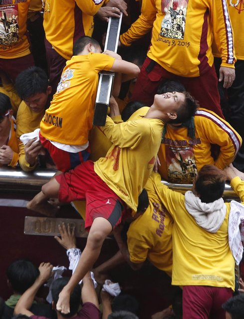 A devotee grimaces while holding the Black Nazarene at the start of an annual procession in Manila, January 9, 2015. (Photo by Erik De Castro/Reuters)