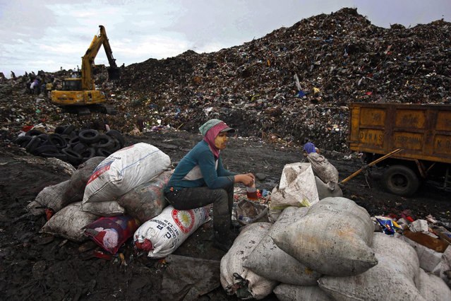 An Indonesian scavenger takes a break after collecting recyclable materials at a dumpsite in Marelan, Medan, North Sumatra Province, Indonesia, 30 November 2015. The United Nations Climate Change Conference, known as COP21, runs from happening from 30 November to 11 December in Paris, with the overall goal of agreeing on a plan to limit the global temperature warming to two degrees Celsius above its current level. (Photo by Dedi Sahputra/EPA)