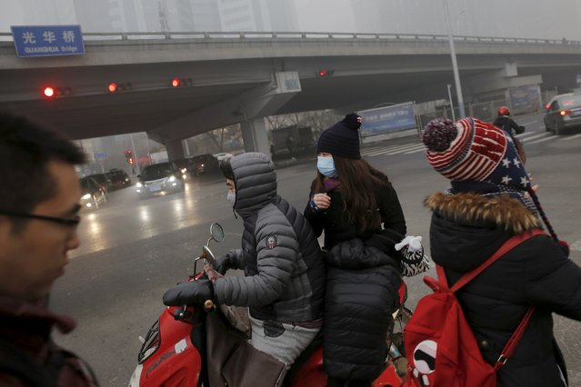 People wear protective masks while riding a moped on an extremely polluted morning as hazardous, choking smog continues to blanket Beijing, China December 1, 2015. (Photo by Damir Sagolj/Reuters)