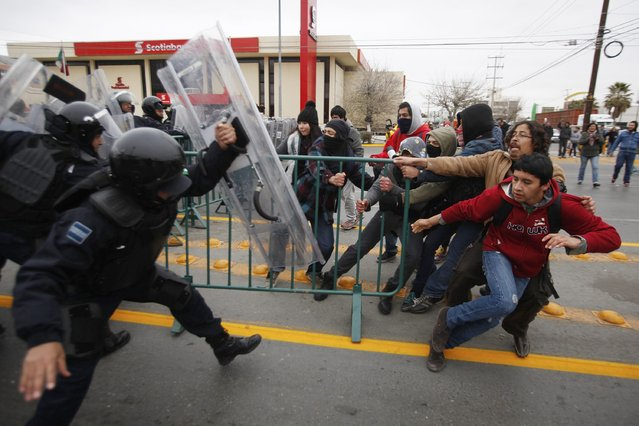 Demonstrators pull a barrier as federal policemen try to stop them during a protest against the visit of Mexico's President Enrique Pena Nieto to the city, in Ciudad Juarez January 14, 2015. (Photo by Jose Luis Gonzalez/Reuters)