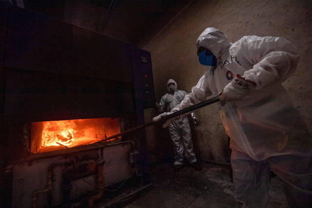 Employees wear protective gear while working at the Azcapotzalco crematorium in Mexico City, on August 6, 2020, amid the COVID-19 coronavirus pandemic (Photo by Pedro Pardo/AFP Photo)