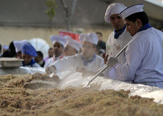 Workers prepare Koshary, a popular Egyptian dish, in an attempt to break the Guinness World Record for the world's biggest plate of Koshary, at a general garden in Zamalek, Cairo, January 17, 2015. (Photo by Mohamed Abd El Ghany/Reuters)