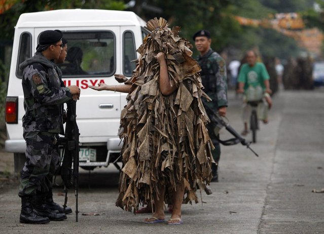 Residents, covered with mud and dried banana leaves, ask for money and candles from police before attending a mass celebrating the feast day of the Catholic patron Saint John the Baptist in the village of Bibiclat, Nueva Ecija, north of Manila, June 24, 2013. Hundreds of devotees took part in this annual religious tradition, which has been held in the village since 1945. (Photo by Cheryl Ravelo/Reuters)