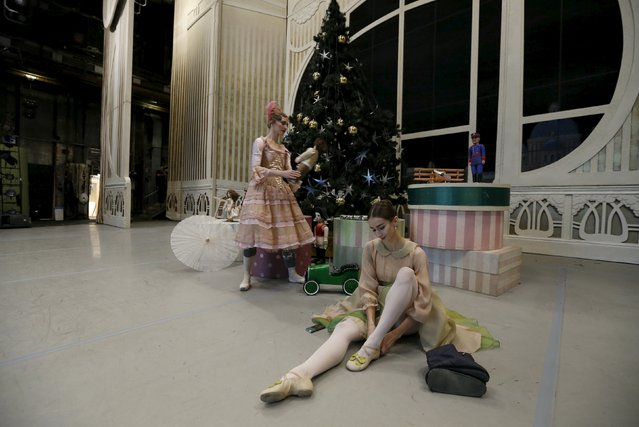 """A ballet dancer puts on her shoes while sitting on a stage behind the curtain before Nacho Duato's """"The Nutcracker"""" at the Mikhailovsky Theatre in St. Petersburg, Russia November 21, 2015. (Photo by Grigory Dukor/Reuters)"""