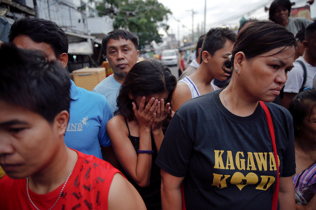 Onlookers react as policemen investigate near the body of a woman killed by unknown gunmen at the market in a port area of Manila, Philippines October 28, 2016. (Photo by Damir Sagolj/Reuters)