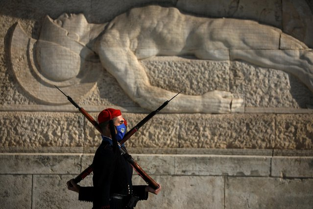 Greek Presidential Guards wearing protective face masks perform their sentry duty in front of the Tomb of the Unknown Soldier, after the Greek government imposed a nationwide lockdown to contain the spread of the coronavirus disease (COVID-19), in Athens, Greece, November 16, 2020. (Photo by Alkis Konstantinidis/Reuters)