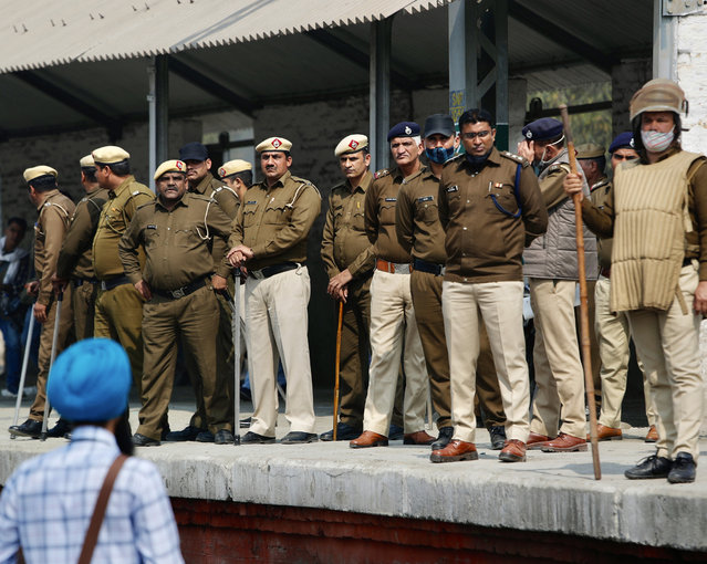 Policemen stand guard as farmers block railway tracks during a protest denouncing three farm laws approved by Parliament in September, in Sonepat, India, Thursday, February 18, 2021. (Photo by Manish Swarup/AP Photo)