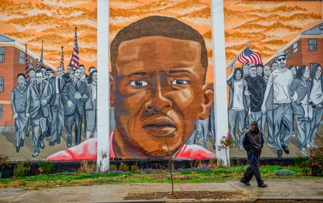 A man, who declined to offer his name, walks past a mural of Freddie Gray in the Sandtown-Winchester neighborhood of Baltimore, December 17, 2015. On Wednesday, Judge Barry Williams declared a mistrial in the case of Police Officer William Porter, one of six officer charged connection with the death of Freddie Gray. (Photo by Bryan Woolston/Reuters)