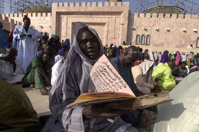 A member of the Mouride Brotherhood, a large Sufi order largely present in Senegal, reads a religious book outside the Great Mosque in Touba on November 19, 2016 during the religious festival of the Magal and the 122 nd edition of celebrations of the return from exile of its founder, the great marabout Sheikh Amadou Baba. This celebration called Magal is characterised by reading the writings of the guide, founder of Mouridism, visiting his descendants and going to the cemetery. (Photo by Seyllou/AFP Photo)