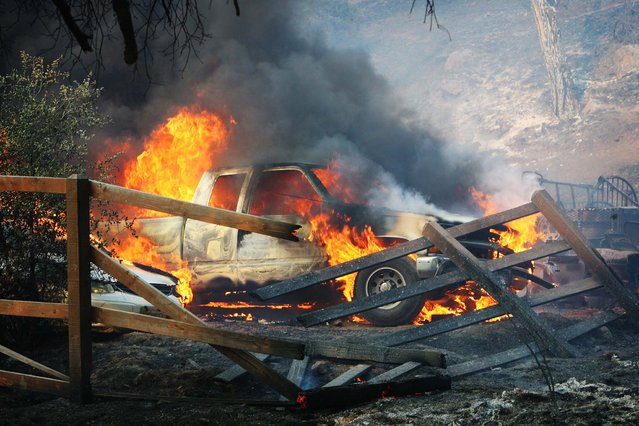 A pickup truck is engulfed in flames as the Silver Fire roars through a residential area near Hwy 243 and Twin Pines Road between Banning and Idyllwild, Calif. on Wednesday, August 7, 2013. (Photo by Frank Bellino/AP Photo/The Press-Enterprise)