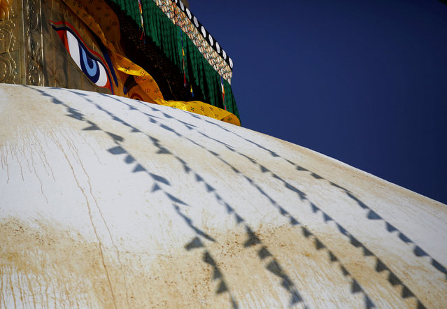 "An ""eye"" is seen behind the prayer flags during the prayers to purify the Boudhanath stupa ahead of its opening on November 22, after it was renovated following last year's earthquake in Kathmandu, Nepal November 18, 2016. (Photo by Navesh Chitrakar/Reuters)"