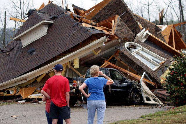 Residents survey damage to homes after a tornado touched down south of Birmingham, Ala. in the Eagle Point community damaging multiple homes, Thursday, March 25, 2021. Authorities reported major tornado damage Thursday south of Birmingham as strong storms moved through the state. The governor issued an emergency declaration as meteorologists warned that more twisters were likely on their way. (Photo by Butch Dill/AP Photo)