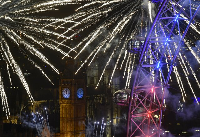 Fireworks explode around the London Eye wheel, the Big Ben clock tower and the Houses of Parliament to mark the beginning of the New Year in London, Britain, January 1, 2016. (Photo by Toby Melville/Reuters)