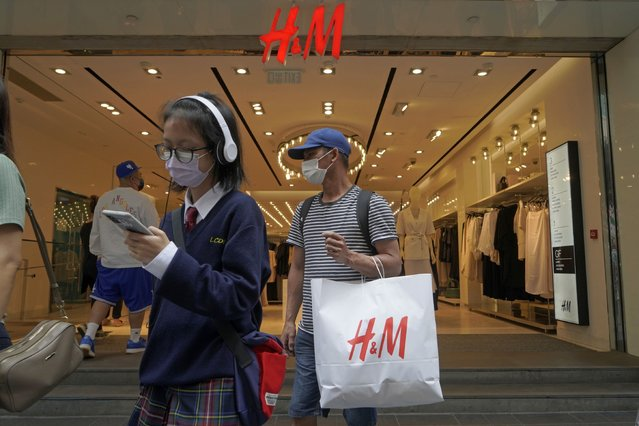 A man shops at an H&M clothing store in Hong Kong, Saturday, March 27, 2021. H&M disappeared from the internet in China as the government raised pressure on shoe and clothing brands and announced sanctions Friday, March 26, 2021, against British officials in a spiraling fight over complaints of abuses in the Xinjiang region. (Photo by Kin Cheung/AP Photo)