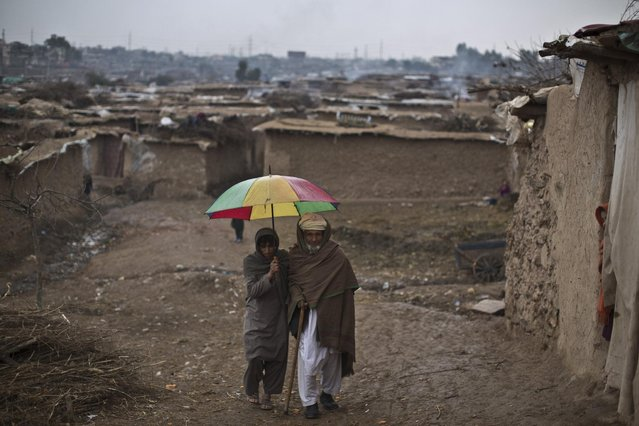 A youth holds an umbrella to shelter an elderly man from rain in a slum that hosts Afghan refugees and internally displaced Pakistanis from tribal areas, on the outskirts of Islamabad, Pakistan, Saturday, February 7, 2015. (Photo by Muhammed Muheisen/AP Photo)
