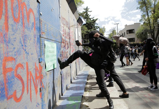 A woman kicks a fence during a protest in support of Victoria Salazar, a Salvadoran woman who died after a Mexican female police officer was seen in a video kneeling on her back, in Mexico City, Mexico on April 2, 2021. (Photo by Raquel Cunha/Reuters)