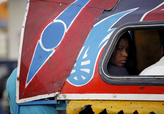 "A woman looks out of a window of a transportation truck called ""Tap Tap"" in Petion Vile in Port-au-Prince February 6, 2015. (Photo by Andres Martinez Casares/Reuters)"