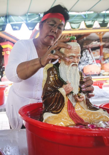 A Balinese woman cleans a statue ahead of the upcoming Chinese New Year at a temple in Denpasar, Bali, Indonesia, 12 February 2015. (Photo by Made Nagi/EPA)