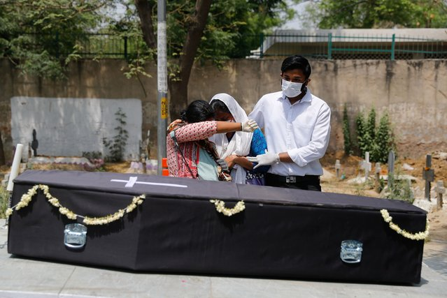 Family members of a person who died from the coronavirus disease (COVID-19) mourn next to the coffin before the burial, at a graveyard in New Delhi, India, April 29, 2021. (Photo by Adnan Abidi/Reuters)