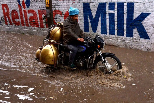 An Indian milkman makes his way through a flooded street after a heavy downpour in Amritsar on February 20, 2015. Temperatures in the city hovered about 14 degrees celsius. (Photo by Narinder Nanu/AFP Photo)