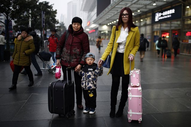 Cui Lihua (L), Li Zihan (C) and Wang Pei (R) pose for a portrait at the Shanghai railway station February 12, 2015. Wang, her mother and son travelled to Henan by train to spend Chinese New Year with the rest of her family. The Chinese Ministry of Transport said a total of 2.807 billion trips are expected to be made during the 40-day Spring Festival travel rush. (Photo by Carlos Barria/Reuters)