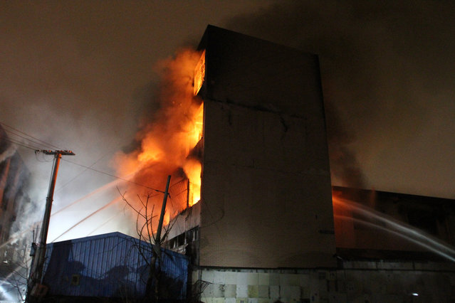 Dense smoke and fire rise as a truck carrying gas bottles get blasted which results in the burning of a joint four-story factory building on January 14, 2016 in Hangzhou, Zhejiang Province of China. The explosion happened in Yuhang District in Hangzhou City at 7:00 p.m was said to be caused by a truck which carried gas bottles and exploded. The Hangzhou Fire Brigade dispatched fire workers to the accident site to control the fire and one was found dead when rescuers arrived at. (Photo by ChinaFotoPress via Getty Images)