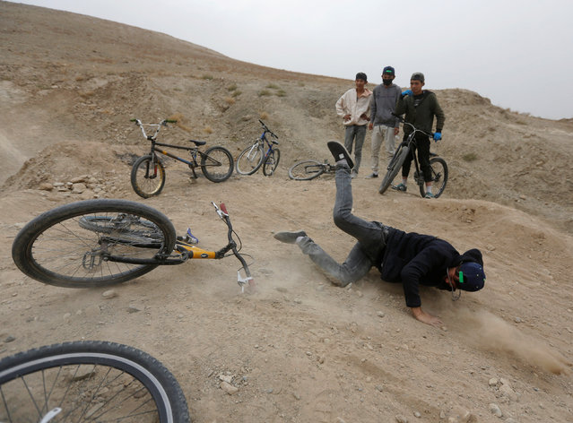 A young Afghan cyclist falls down from his bicycle during an exercise on the outskirts of Kabul, Afghanistan November 20, 2016. (Photo by Omar Sobhani/Reuters)