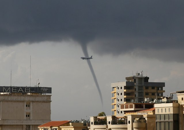 A waterspout forms over the Mediterranean Sea as a passenger jet descents to land at Beirut-Rafic Hariri International Airport in Beirut January 1, 2015. (Photo by Jamal Saidi/Reuters)