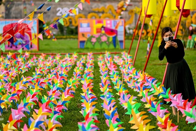 A woman takes photographs with her mobile phone amidst colourful pinwheels at the Thang Long imperial citadel in Hanoi on March 14, 2021. (Photo by Manan Vatsyayana/AFP Photo/Profimedia)