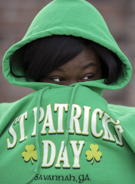 Chizzy Odimgbe keeps warm before the start of the St. Patrick's Day parade, Tuesday, March 17, 2015, in Savannah, Ga. The St. Patrick's Day tradition in Savannah dates back to the first parade held on March 17, 1824. While Savannah has been celebrating St. Patrick's Day for 191 years, there have been at least six years without a parade. (Photo by Stephen B. Morton/AP Photo)