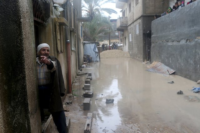 A Palestinian man gestures as flood waters are seen outside his house during a winter storm in Rafah in the southern Gaza Strip, January 26, 2016. (Photo by Ibraheem Abu Mustafa/Reuters)