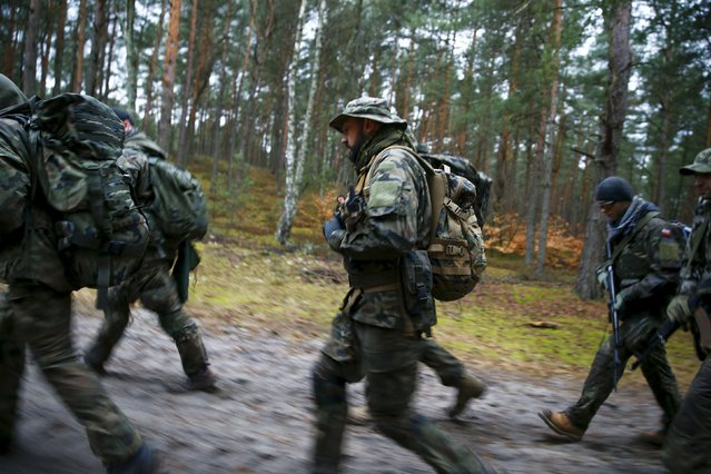 People take part in an endurance march during a territorial defence training organised by paramilitary group SJS Strzelec (Shooters Association) in the forest near Minsk Mazowiecki, eastern Poland March 14, 2014. (Photo by Kacper Pempel/Reuters)