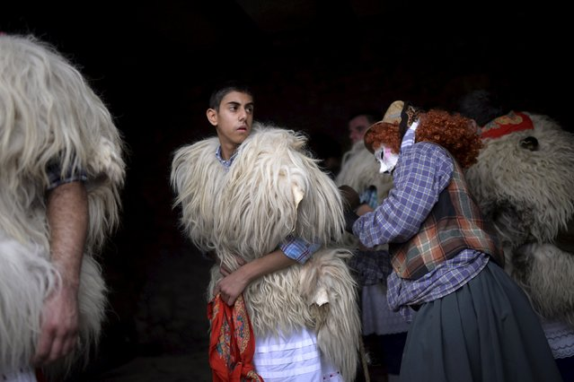A dancer is helped with his costume during carnival celebrations in Ituren February 1, 2016. Bell carrying dancers known as Joaldunak from Zubieta and neighbouring Ituren visit each other's villages performing a ritual dance to ward off evil spirits and awaken the coming spring. Alongside the dancers, villagers dress in bizarre and frightening costumes to harass and scare visitors. (Photo by Vincent West/Reuters)