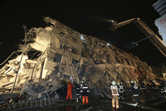 Rescue workers search a toppled building after an earthquake in Tainan, Taiwan, Saturday, February 6, 2016. (Photo by AP Photo)