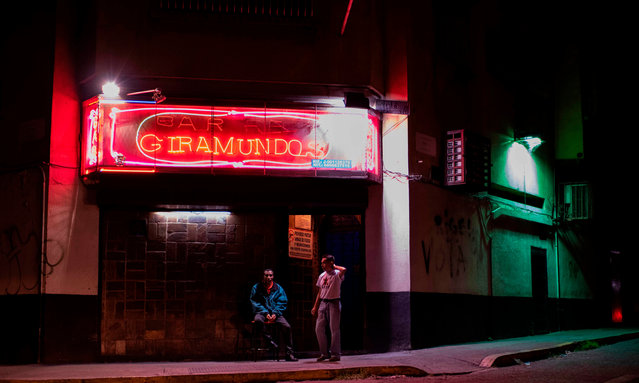 Employees are pictured at the entrance of a bar in an empty street of Caracas, on October 16, 2018. When the sun goes down, loneliness reigns in the streets of Caracas, punished by unbridled crime and the economic crisis. According to NGOs, some 26,000 violent deaths were recorded in 2017 in Venezuela, with a rate of 89 per 100,000 inhabitants, 15 times higher than the world average. (Photo by Ronaldo Schemidt/AFP Photo)