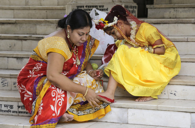 """A Hindu woman decorates the sole of her daughter's feet with vermillion for her to participate in a ceremony where young girls are worshipped as """"Kumari"""", or living goddess, during Ram Navami festival, at a temple in Kolkata, India, Saturday, March 28, 2015. Ram Navami marks the birth of Hindu God Rama. (Photo by Bikas Das/AP Photo)"""