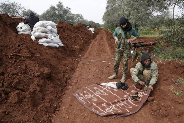 Rebel fighters from the Ahrar al-Sham Islamic Movement prepare their ammunition during what they said was an offensive to take the northwestern city of Idlib March 24, 2015. (Photo by Khalil Ashawi/Reuters)