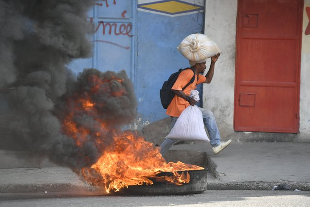 A man runs past a tire set on fire by protesters upset with growing violence in the Lalue neighborhood of Port-au-Prince, Haiti, Wednesday, July 14, 2021. (Photo by Matias Delacroix/AP Photo)