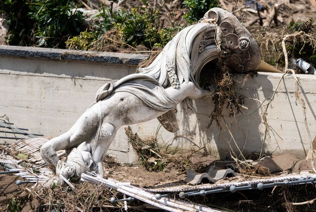 A statue lies amidst rubble and debris in Marienthal, Rhineland-Palatinate on July 18, 2021. The small village was largely destroyed. (Photo by Boris Roessler/dpa)