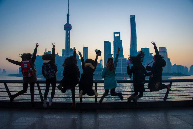 People view the sunrise scene at the Bund in Shanghai, east China, January 1, 2017. (Photo by Wang Hechun/Xinhua/Barcroft Images)